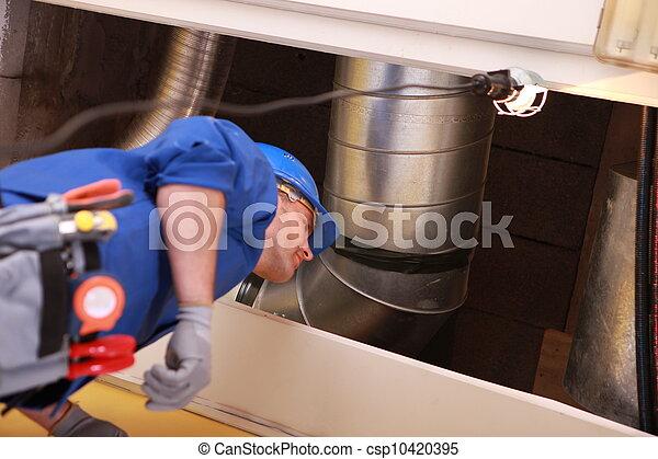 Plomero parado bajo un conducto de calefacción - csp10420395