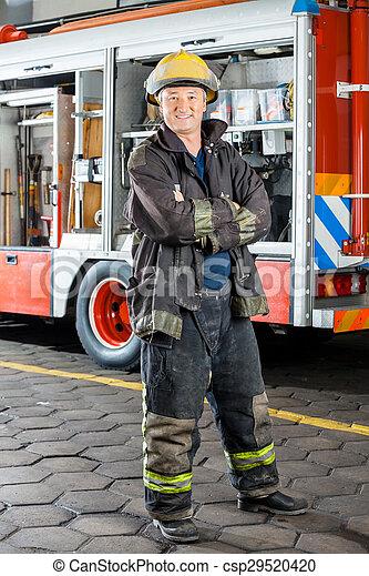 Feliz bombero parado contra el camión - csp29520420