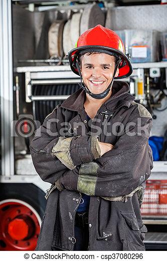 Bombero feliz con los brazos cruzados contra el camión de bomberos - csp37080296