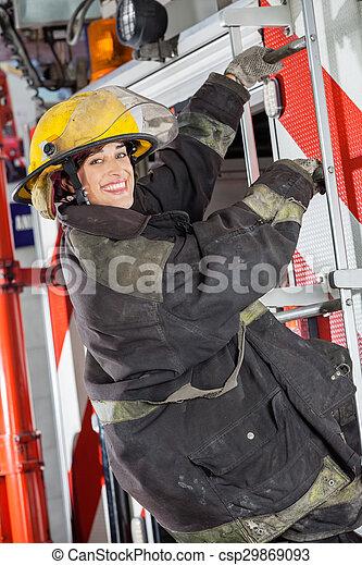 Feliz bombero parada en el camión en la estación de bomberos - csp29869093