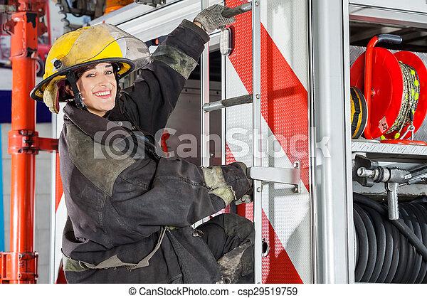 Bombero sonriente parado en un camión en la estación de bomberos - csp29519759