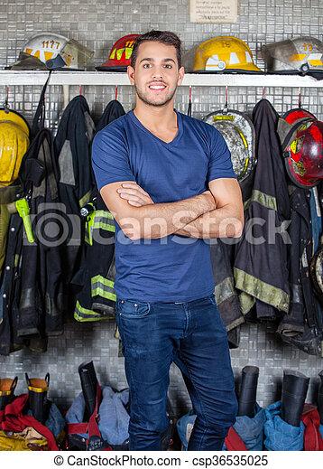 Bombero sonriente parado en la estación de bomberos - csp36535025