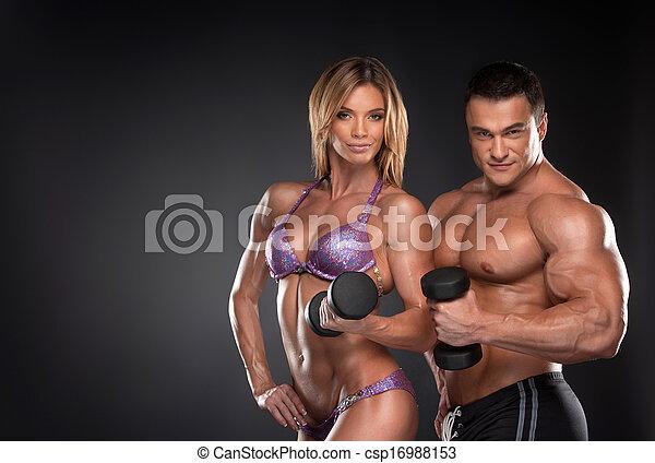 Un par de culturistas bien entrenados con pesas. Mujer y hombre de pie sobre fondo negro - csp16988153