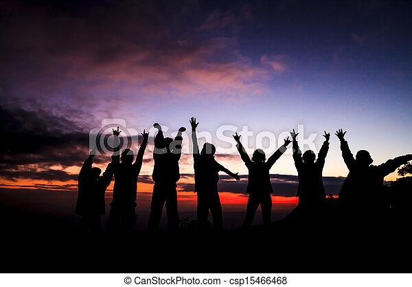 Silueta de un grupo de amigos parados en el atardecer - csp15466468