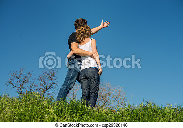 Una pareja joven parada en una playa - csp29320146