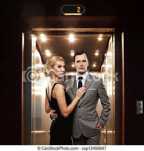 Pareja retro de pie contra el ascensor. - csp12456647