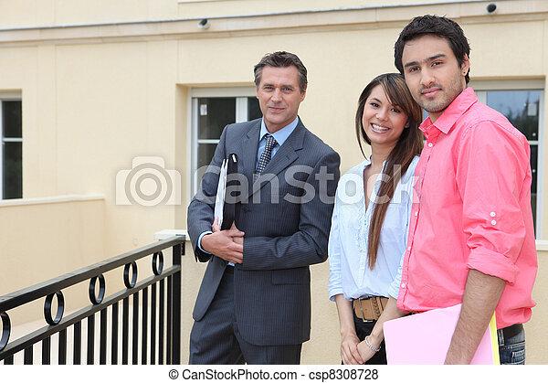 Una pareja parada fuera de una casa con un agente inmobiliario - csp8308728