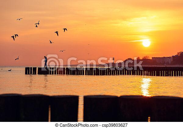 La silueta de un hombre de pie en un rompeolas contra el cielo al amanecer - csp39803627