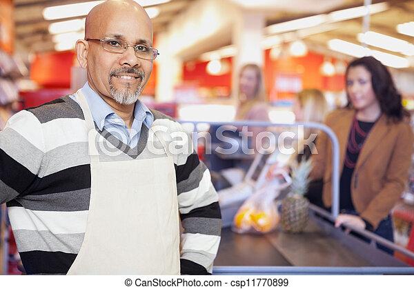 Cajero de la tienda de comestibles parado en la caja registradora - csp11770899