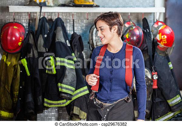 Bombero de pie contra los uniformes en la estación de bomberos - csp29676382