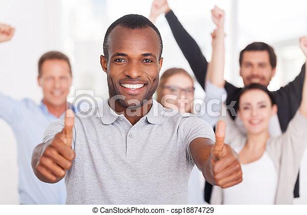 Feliz equipo de negocios. Un joven africano feliz mostrando sus pulgares hacia arriba y sonriendo mientras un grupo de personas de ropa casual de pie en el fondo - csp18874729