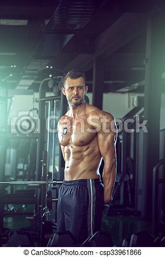 Ein Mann, der in der Turnhalle posiert - csp33961866