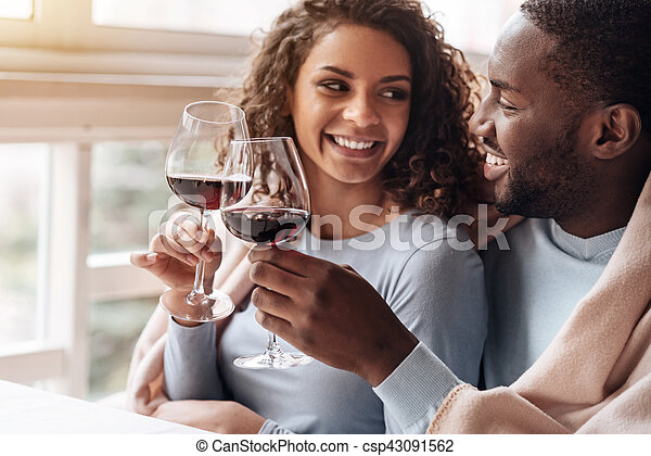 Positive African American couple holding wineglasses in the restaurant - csp43091562