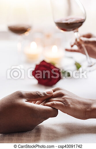 Positive African American couple holding hands in the cafe - csp43091742