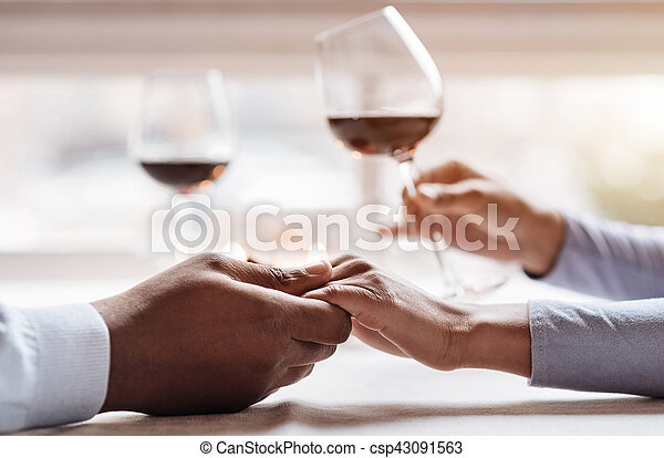 Positive African American couple enjoying the beverage in the restaurant - csp43091563