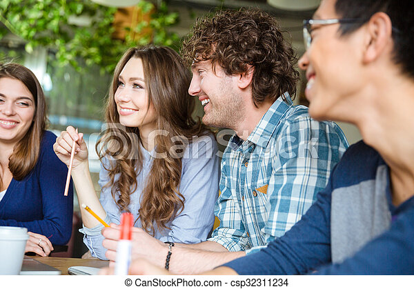 Positive cheerful students studying together  - csp32311234