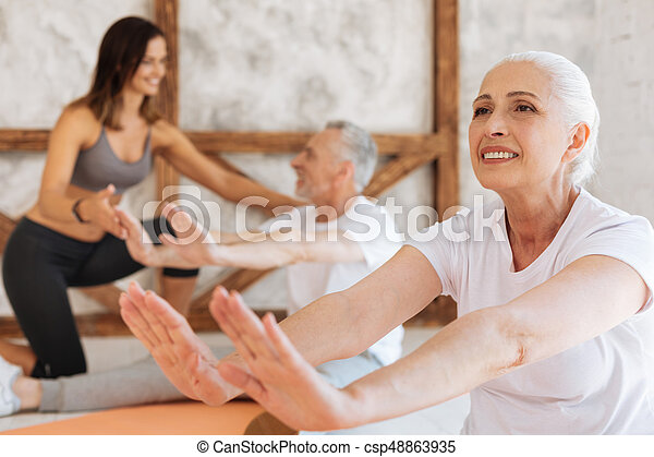 It is easy. Healthy woman feeling happiness while doing sport and sitting in semi position