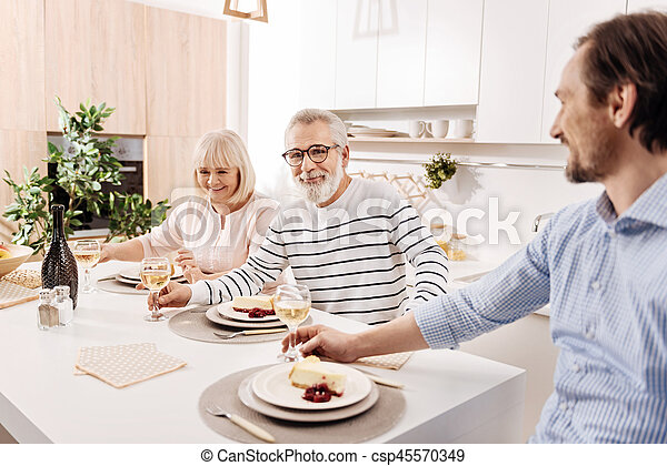 Positive elderly parents enjoying weekend with son at home - csp45570349