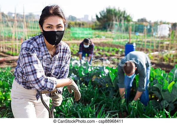 Positive female gardener posing in backyard garden - csp88968411