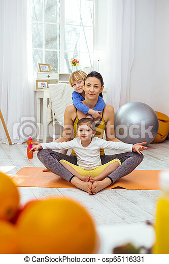Positive nice woman sitting in the lotus pose - csp65116331