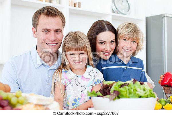 Positive parents preparing dinner with their children in the kitchen - csp3277807