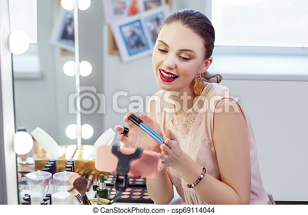 Positive pretty woman holding her professional mascara - csp69114044