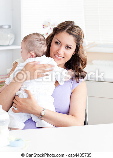 Positive young mother holding her baby in the kitchen - csp4405735
