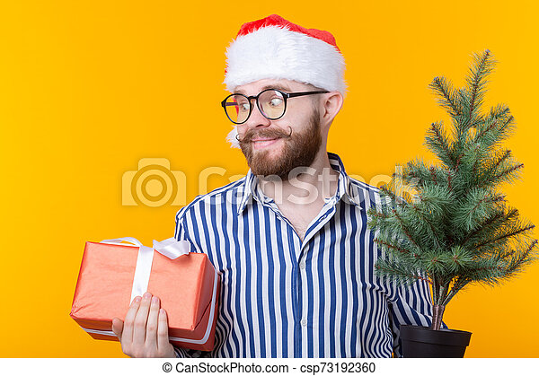 Un joven Santa Claus con regalos y un árbol de Navidad posando en un fondo amarillo. El concepto de Navidad y Año Nuevo. - csp73192360