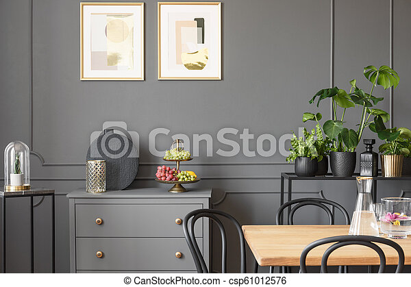 Posters above grey cabinet in dark dining room interior with plants and wooden table. Real photo - csp61012576