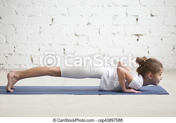 niña en pose de chaturanga dandasana estudio blanco