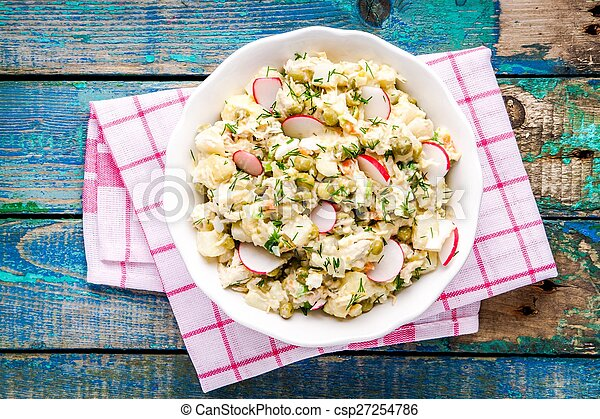 potato salad with fresh radishes in a white bowl top view - csp27254786