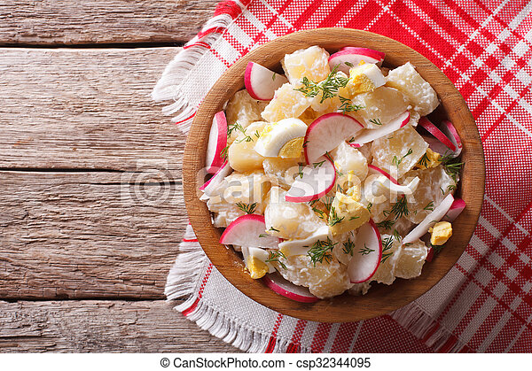 potato salad with radish and eggs in a bowl. horizontal top view - csp32344095
