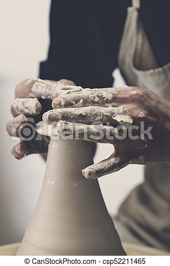 Potter makes pottery handmade in the workshop - csp52211465