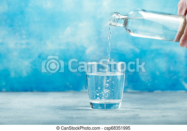 Pouring water from bottle into glass - csp68351995