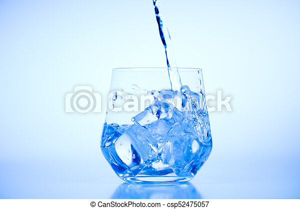 Pouring water from plastic bottle into a glass with ice on light blue background - csp52475057