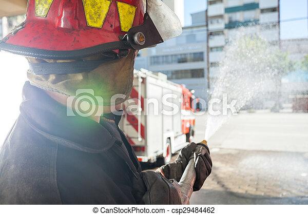 Bombero rociando agua mientras practican en la estación de bomberos - csp29484462