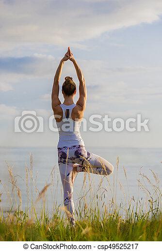Mujer en forma caucásica practicando yoga - csp49525217