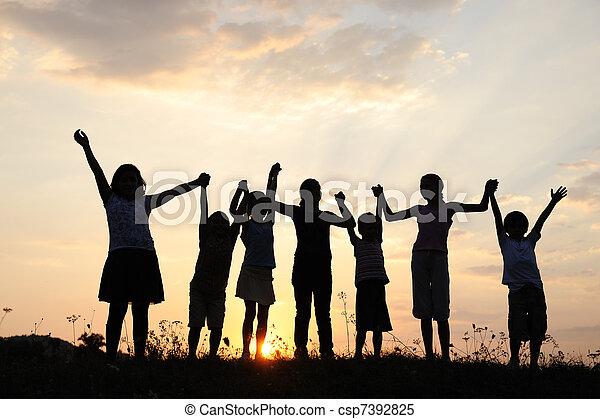Silueta, grupo de niños felices jugando en la pradera, atardecer, verano - csp7392825