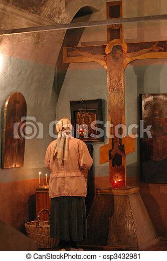 Pray god at crucifix in a church religion scene - csp3432981