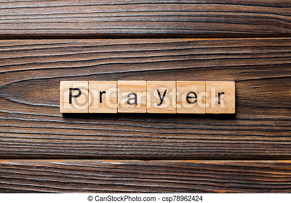 PRAYER word written on wood block. PRAYER text on wooden table for your desing, concept - csp78962424