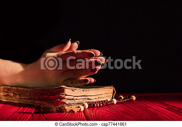 Praying hands on bible and rosary. - csp77441661