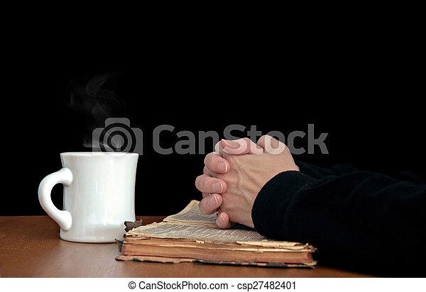 praying hands on worn Bible - csp27482401