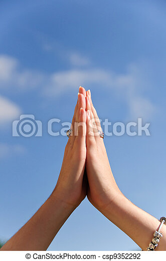 praying hands hands praying in front of a blue sky