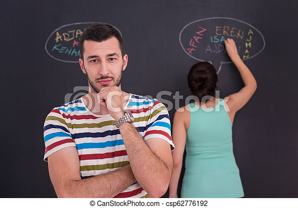 pregnant couple writing on a black chalkboard - csp62776192