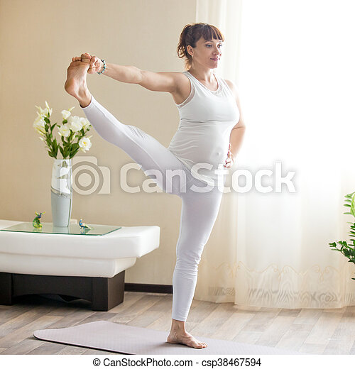 pregnant woman doing extended hand to big toe yoga pose at