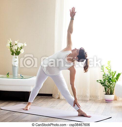 pregnant woman doing utthita trikonasana yoga pose at home