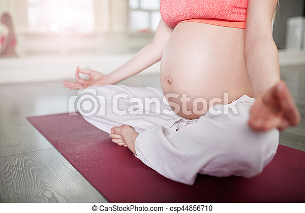 pregnant woman meditating in yoga pose cropped portrait