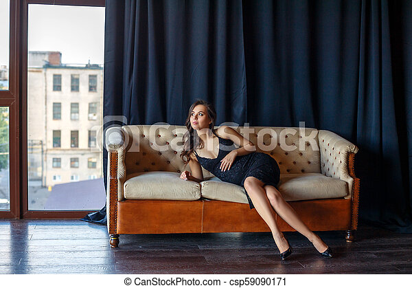 pregnant woman sitting on the couch in a beautiful dress - csp59090171
