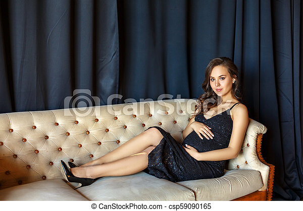 pregnant woman sitting on the couch in a beautiful dress - csp59090165