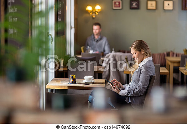 Pregnant Woman Using Digital Tablet At Cafe - csp14674092